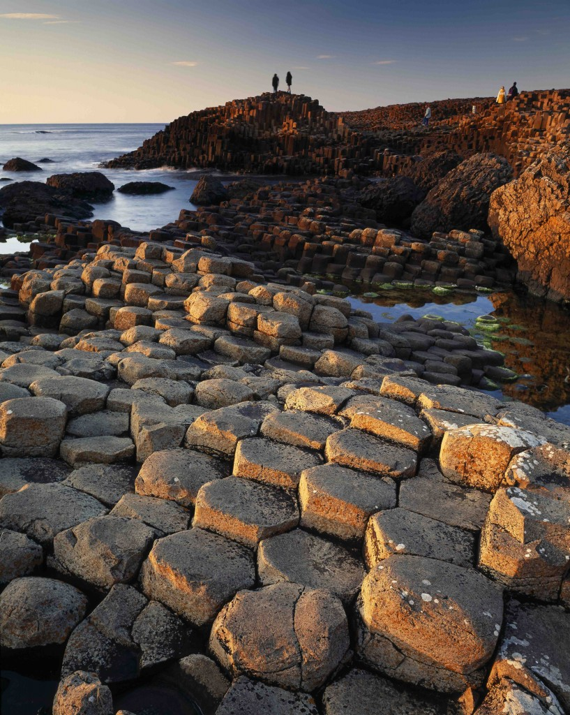 The Giant's Causeway, County Antim, Northern Ireland, is a geological phenomenon renowned for its polygonal columns of layered basalt, caused by a volcanic eruption 60 million years ago